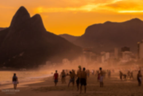 Landscape photograph of a sunset at the famous Ipanema Beach in Rio De Janeiro, Brazil with the Dois Irmaos mountain in the background and Brazilians playing beach football