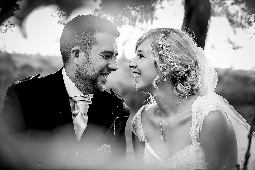 A happy groom and bride smiling at each other while sat outside in a field on their wedding day in Cardiff, South Wales