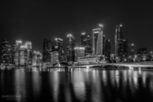 Black and white street photograph of a shot of a cityscape scene of the Singapore skyline in Singapore
