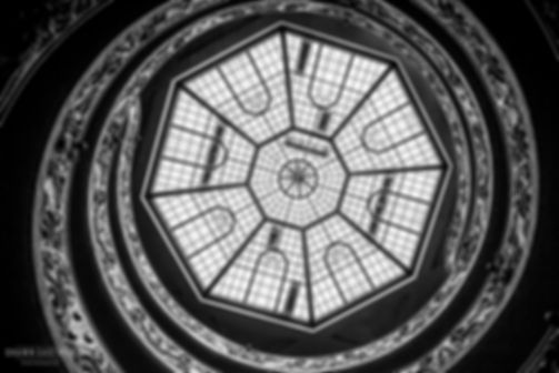 Black and white street photograph of a shot looking up at the dome above the Bramante staircase in the Vatican Museums in the Vatican City, Vatican, Italy