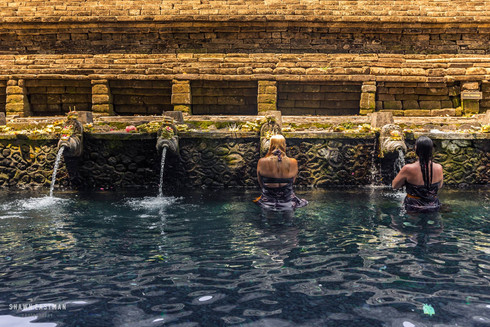 two-female-tourists-washing-holy-water-t