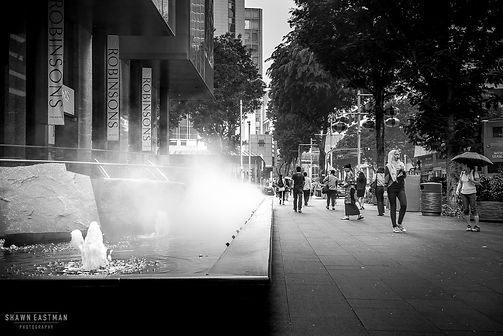 Street photograph of a street scene with a fountain feature in Singapore.