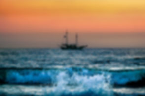 Landscape photograph of the sunset in Paphos, Cyprus with a ship sailing in the ocean