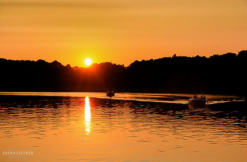 Landscape photograph of a sunset on Kentucky Lake in Paducah, Kentucky, USA with two small boats sailing off into the distance