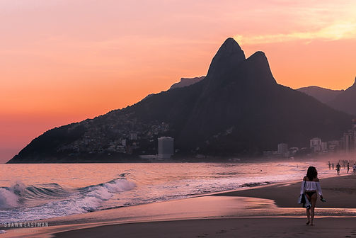 Landscape photograph of a sunset at the famous Ipanema Beach in Rio De Janeiro, Brazil with the Dois Irmaos mountain in the background and a lady walking on the beach