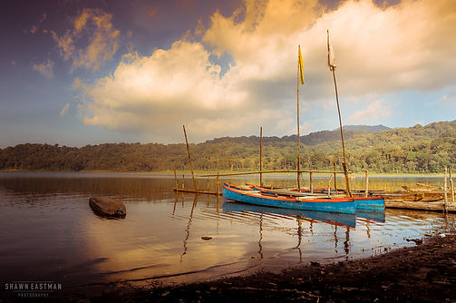 Landscape photograph of sunset at Danau Tamblingan, with some small fisherman boats on the lake in Bali, Indonesia