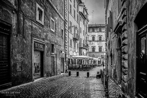 Black and white street photograph night shot of a scene in Rome, Italy