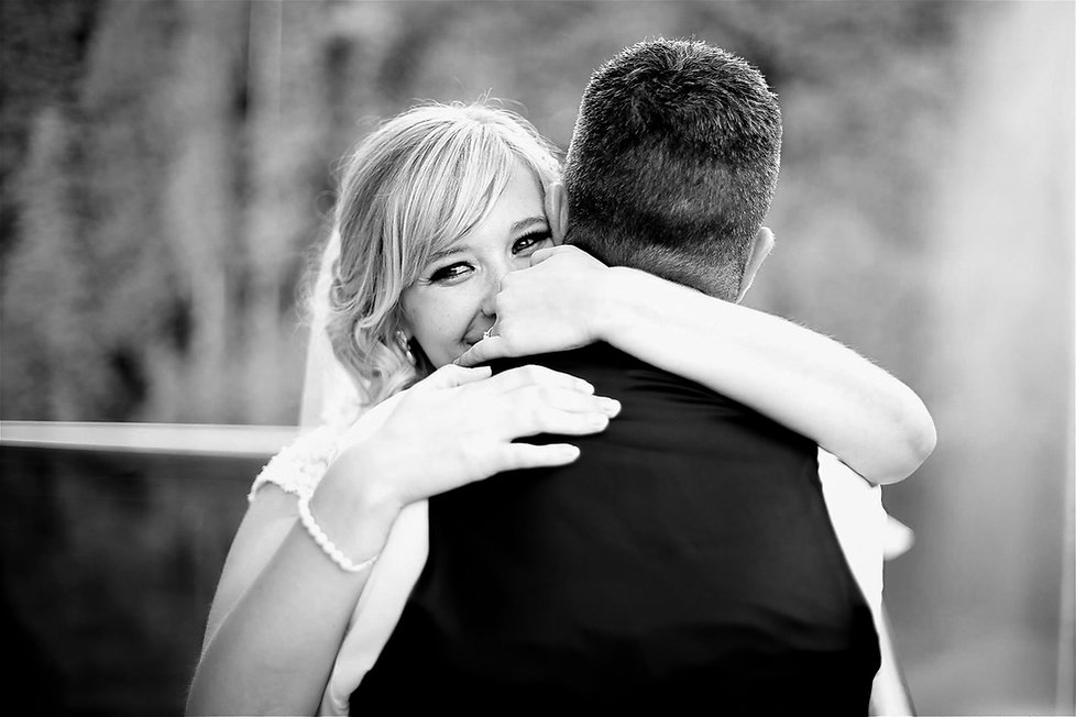 A happy bride hugging her husband on their wedding day in Cardiff, South Wales