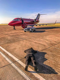 Professional photographer Shawn Eastman photographing Mercedes-Benz 280SL and red private jet at Cardiff Airport