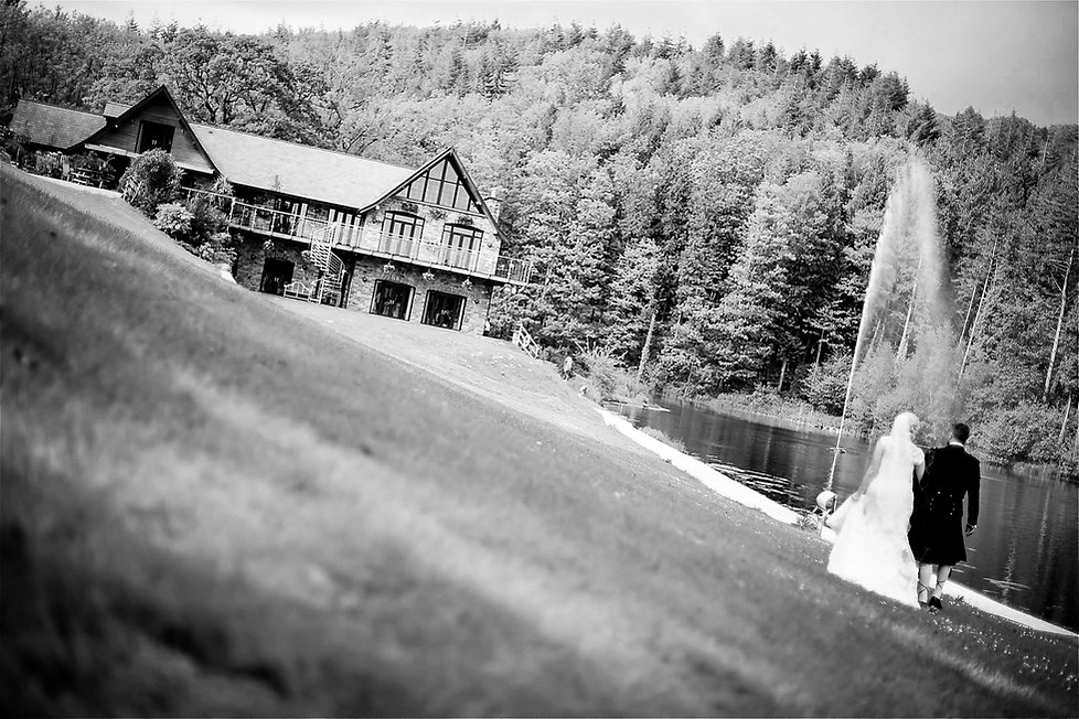 A newly-wed bride and groom walking on grass outside Canada Lodge & Lake on their wedding day in Cardiff, South Wales
