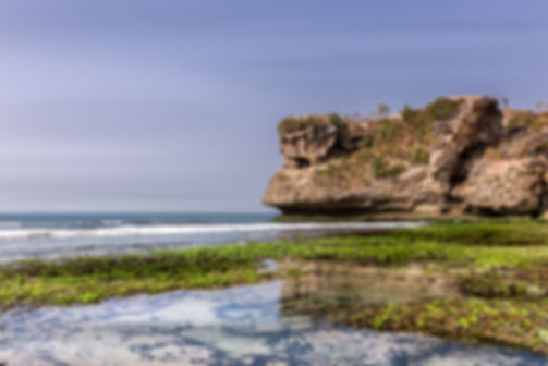 Landscape photograph of a large rock on the coastline of Bali, Indonesia