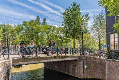 tourists-on-bridge-bicycles-canal-amster