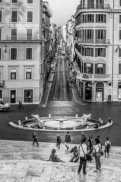 Black and white street photograph of a street scene at the Spanish steps in the morning in Rome, Italy