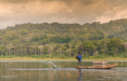 Landscape photograph at Danau Tamblingan in Bali, Indonesia, with a fisherman fishing on the lake
