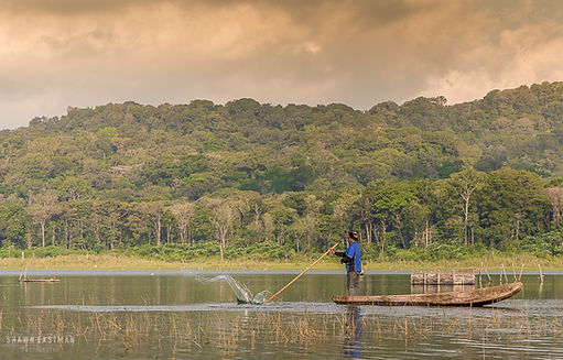 Landscape photograph at Danau Tamblingan in Bali, Indonesia, with a fisherman fishing on the lake