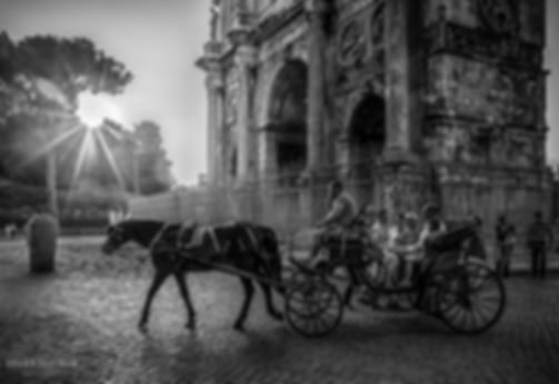 Black and white street photograph of a horse and carriage at sunset beside the Arch of Constantine in Rome, Italy