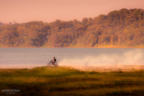 Landscape photograph of sunset at Danau Tamblingan with a Balinese youngster riding a motorbike on the fields in Bali, Indonesia