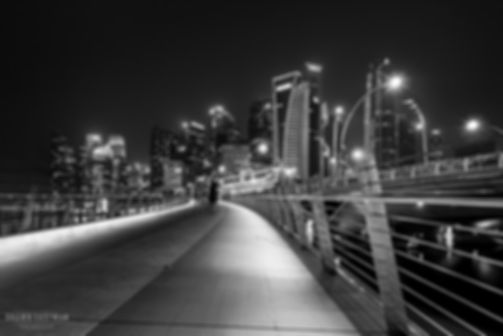 Black and white street photograph of a shot of a night scene of the Singapore skyline from a bridge in Singapore