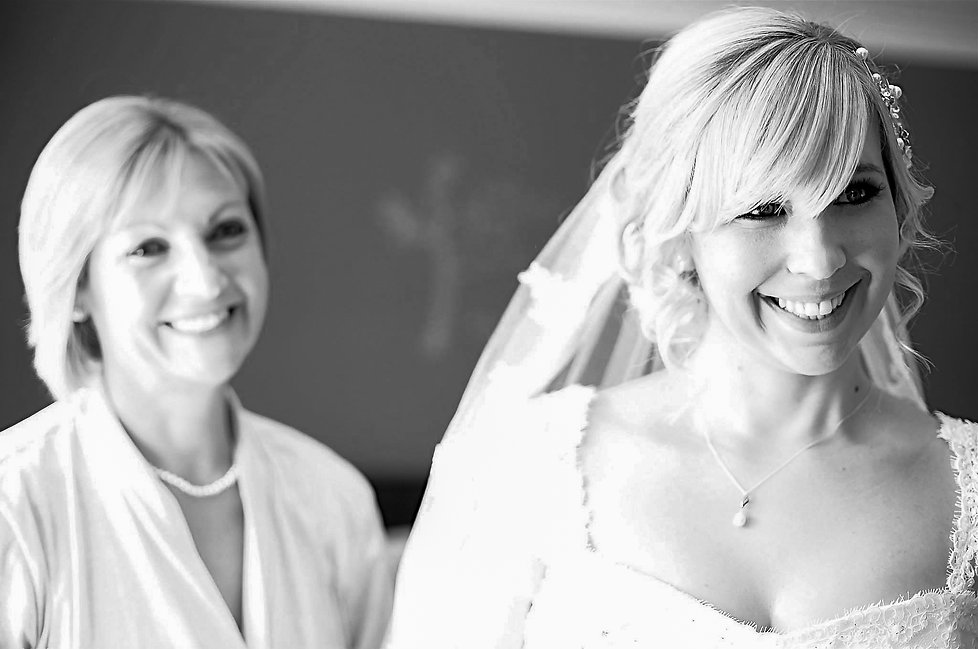 A smiling mother behind her smiling bride daughter on the morning of her wedding day in Cardiff, South Wales