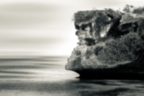 Black and white landscape photograph of a large rock formation on the coastline in Bali, Indonesia