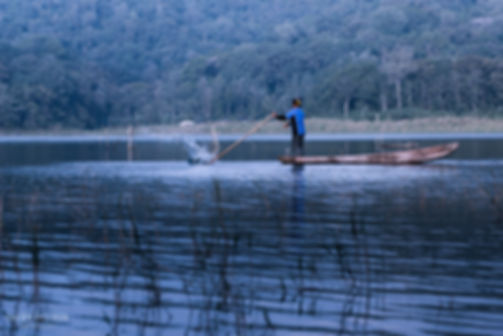 Landscape photograph of a fisherman fishing on Danau Tamblingan in Bali, Indonesia