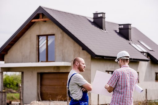 Builders looking at design plans outside a home renovation project in Cardiff, South Wales