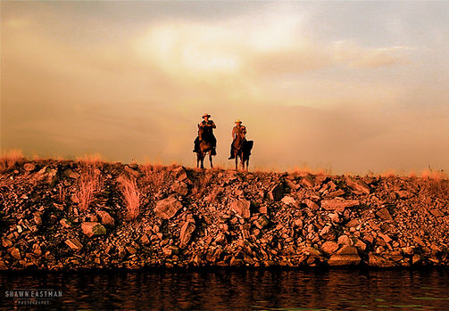 Landscape photograph of a sunset in Paducah, Kentucky, USA with two cowboys on horseback