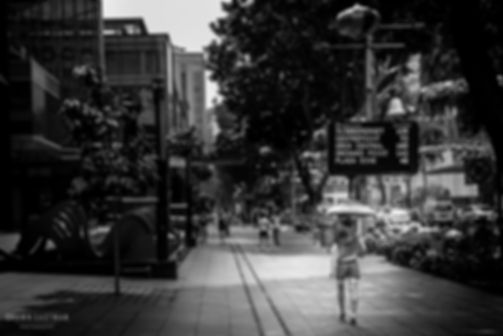 Street photograph of a street scene with a singaporean girl walking with an umbrella in Singapore.