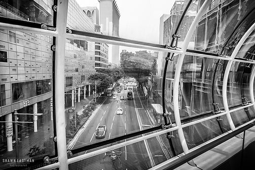 Street photograph looking at the road below through windows of a bridge linking two malls together.