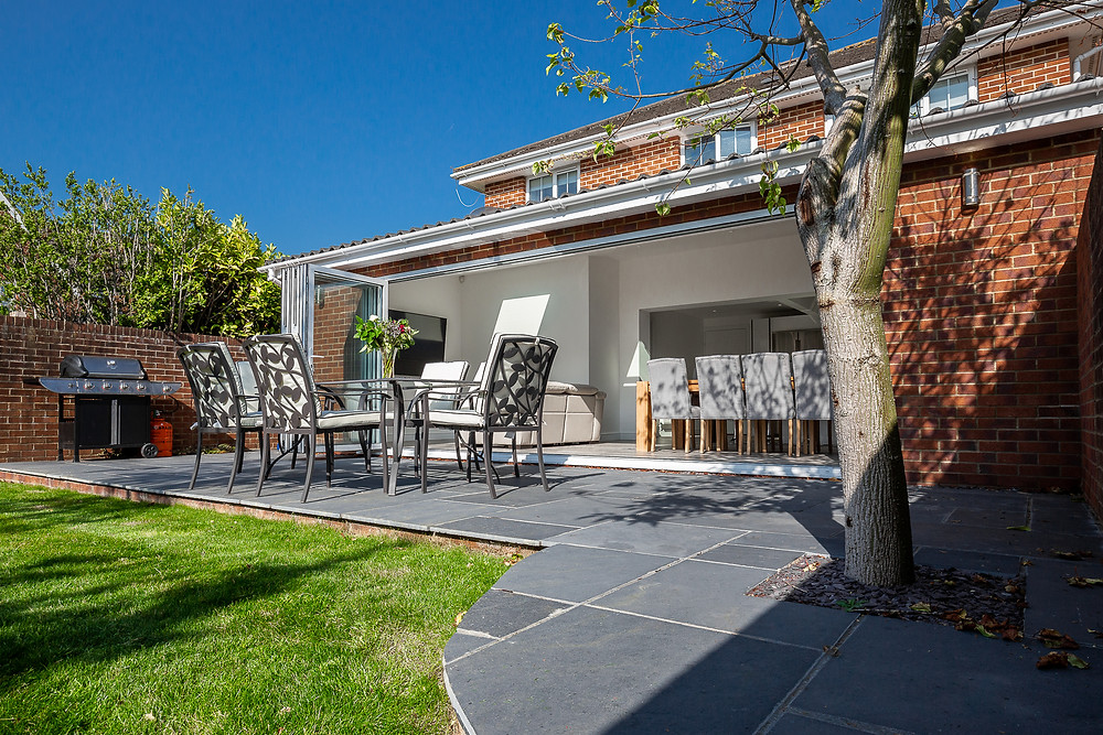 A newly installed grey concrete tile patio in the garden of a property in Cardiff, South Wales