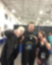 """Jon and Tim Hughes presenting a Hardway Podcast t-shirt to Arlene James after beating """"Good News"""" at air hockey during WrestleCon 2013 weekend (Jon's Personal Photos)"""