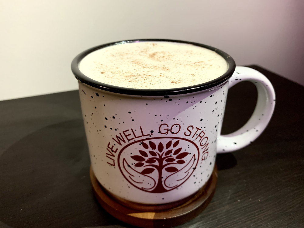 A mug holding a London fog latte with whipped cream on top
