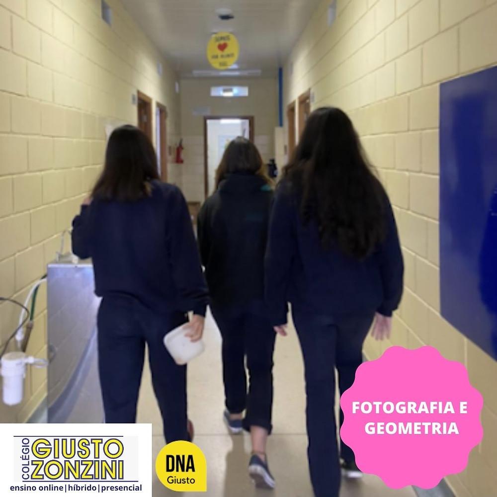 #PraCegoVer Fotografia - Em um corredor, teto branco e paredes amarelas, três alunas trajando um uniforme azul do colégio andam juntas, uma um pouco mais para frente em direção às portas ao fundo, à esquerda delas vemos um bebedouro, e na parede à direita há um quadro azul. Fim da descrição