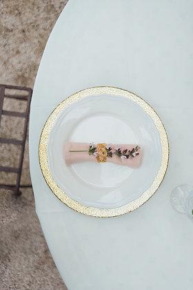Onderbord met gouden rand en lichtroze servet met rozemarijn