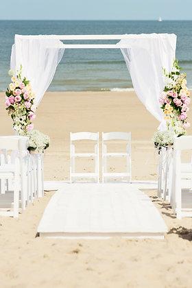 een wit prieel met witte doeken versierd met bloemen op het strand en witte klapstoelen