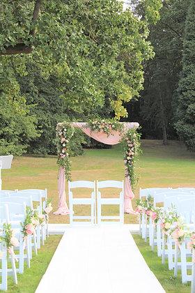 Romantisch prieel in een bos met lichtroze doeken en witte klapstoelen