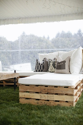 Lounge paletten met witte zitkussens en sierkussens in gras