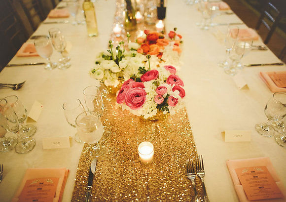 Tafelloper in goudkleur versierd met theelichtjes en bloemen