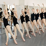 Young ballerinas doing exercises in studio. Young ballet actresses training dance move at