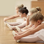 Group of beautiful little ballerinas doing exercises on the floor.jpg