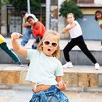 Portrait of emotional girl doing hip hop movements during open air group dance class.jpg