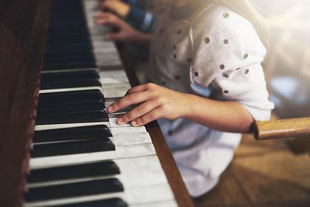 Eine Kinderhand folgt den technischen Tipps des Klavierlehrers