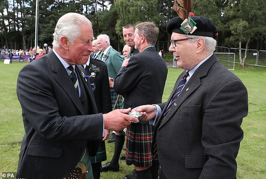 Former President of Clan Farquharson UK, Alan Caig, presents HRH Prince Charles, Duke of Rothesay, with a dram of Laphroaig at the 2019 Ballater Highland Games