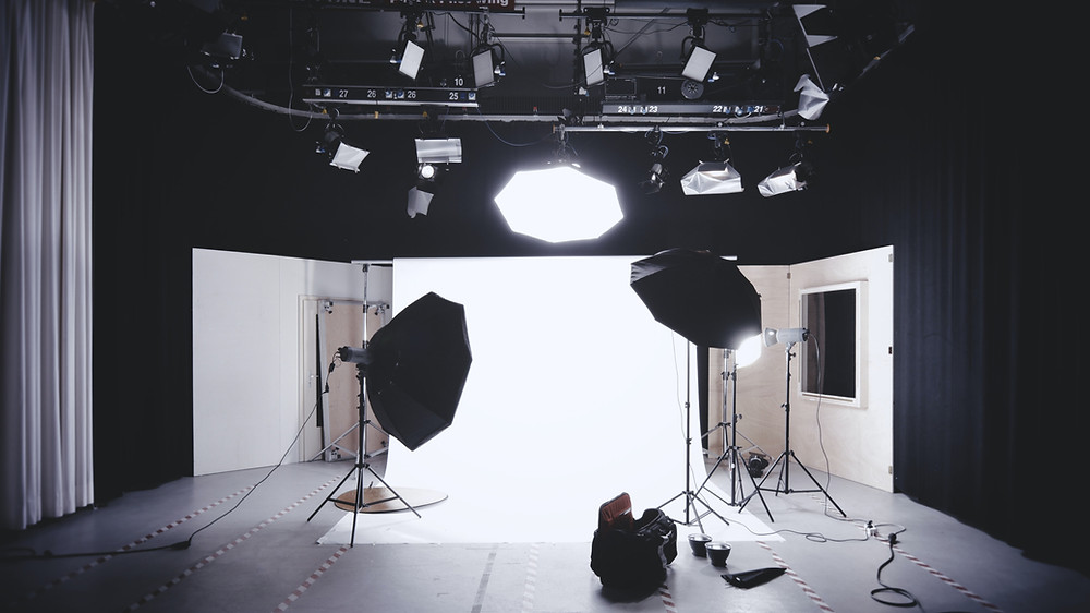 Empty Black & White Photo Shoot Set Up with lighting equipment and white backdrop. Ref: Pexels