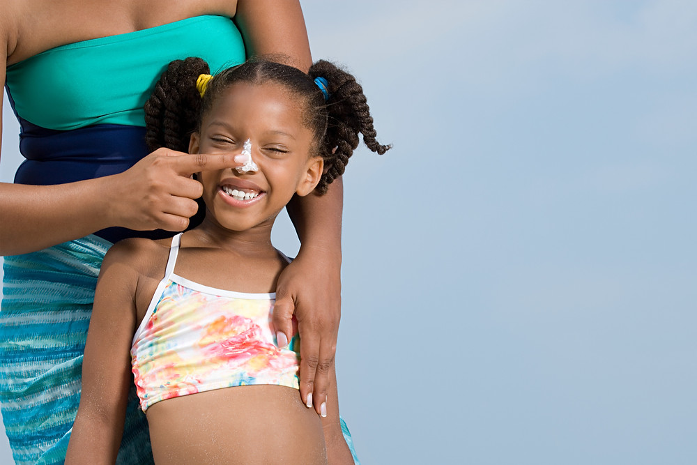 A young black girl smiling in a bikini at the beach, her mum puts suncream on her nose