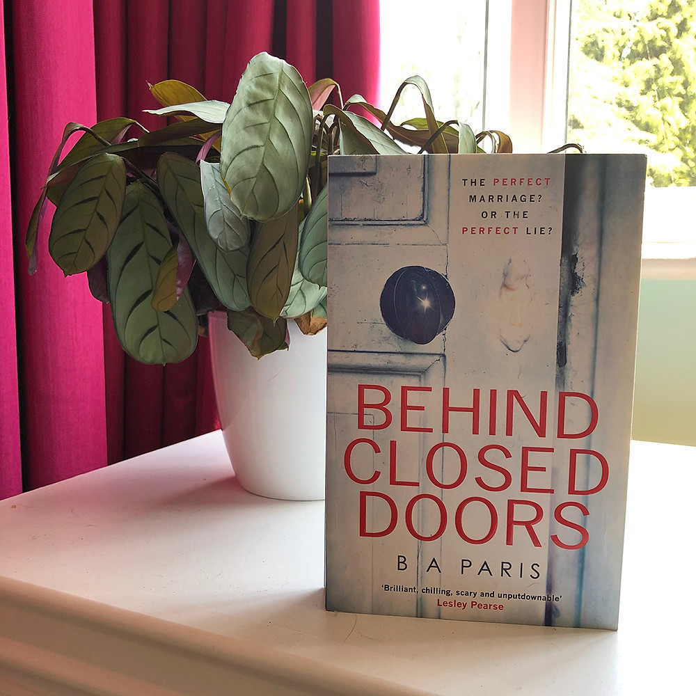 Behind Closed Doors by B.A. Paris by a plant and window