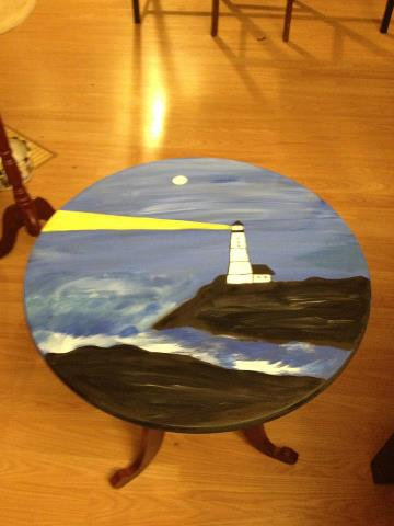 Light house painting on round accent table