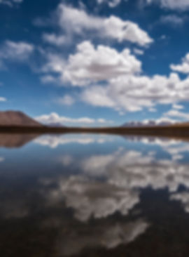 A high mountain lake in southwestern Bolivia reflects blue sky and clouds.