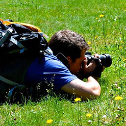 Aaron taking photos in the green grass of British Columbia, Canada