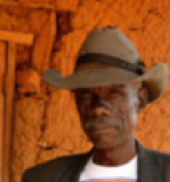 An African man with leathery face and mustache wears a weathered cowboy hat outside a mud hut in western Kenya.